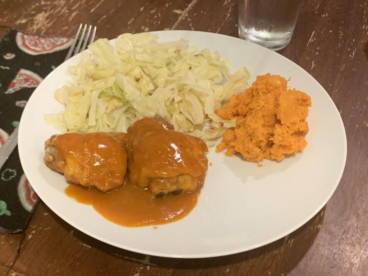 Image shows a white plate with a pizza-themed napkin and fork off to the side. On the plate sits two orange drenched chicken thighs, a mound of orange yams, and a pile of green-ish slivered cabbage.