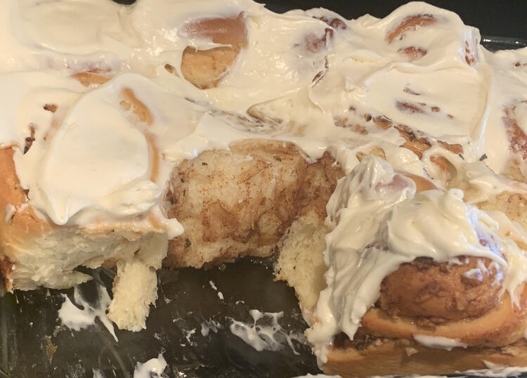Image shows the white frosting coated cinnamon buns with a couple missing showing off the soft and fluffy interior.
