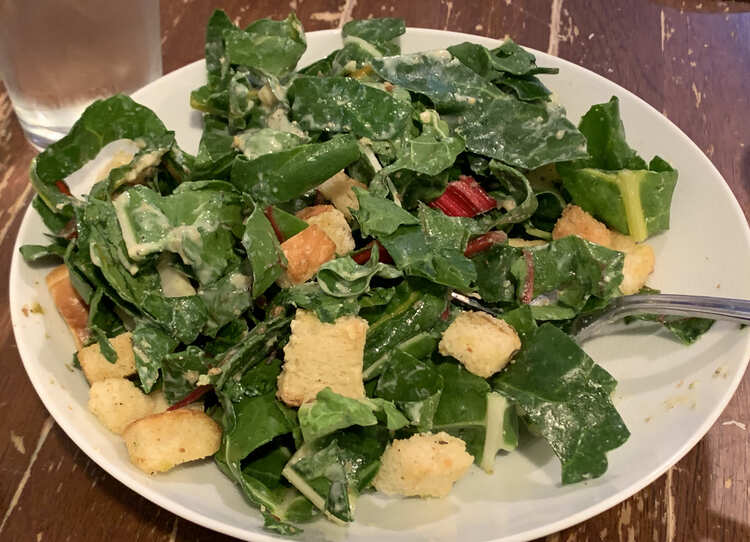 Image shows a wide open bowl filled with Caesar salad, a fork, and a glass of water in the background.