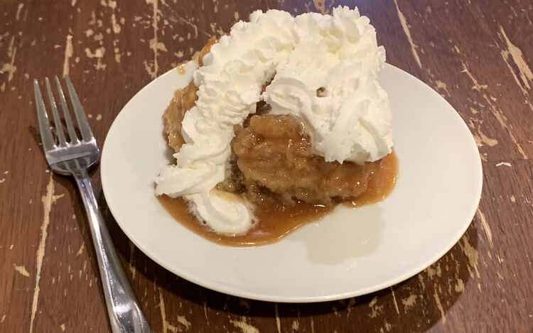 Image shows a piece of sticky bun on a white plate with a pool of caramel. The bun is coated in whip cream and a fork sits beside the saucer about to be picked up.