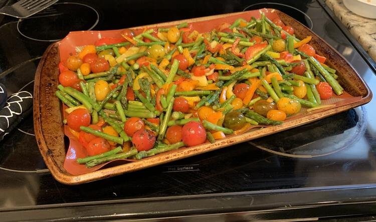 Image shows a variety of cherry tomatoes and pieces of asparagus laid out on a single cookie sheet laid out horizontally on the stove top. Beside it sits and oven mitt and, to the back, a metal flipper to later serve it with.