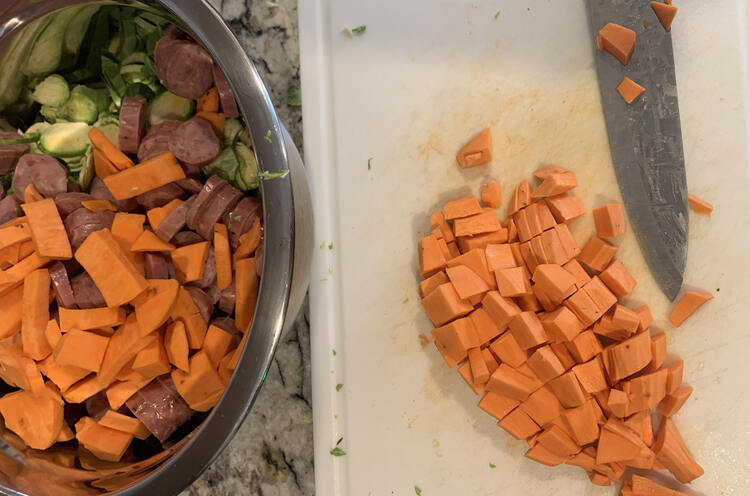 Image shows a white plastic cutting board holding diced yams and a dirtied knife. Beside it sits a large metal bowl partway filled with sliced Brussel sprouts, sliced sausages, and the rest of the yams.