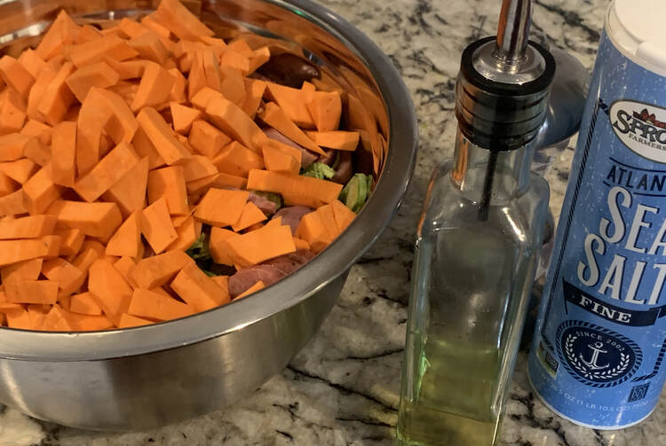Image shows the same metal bowl although you can hardly see the Brussel sprouts and sausages through the yams. Beside it sits an oil dispenser, sea salt, and a pepper mill.