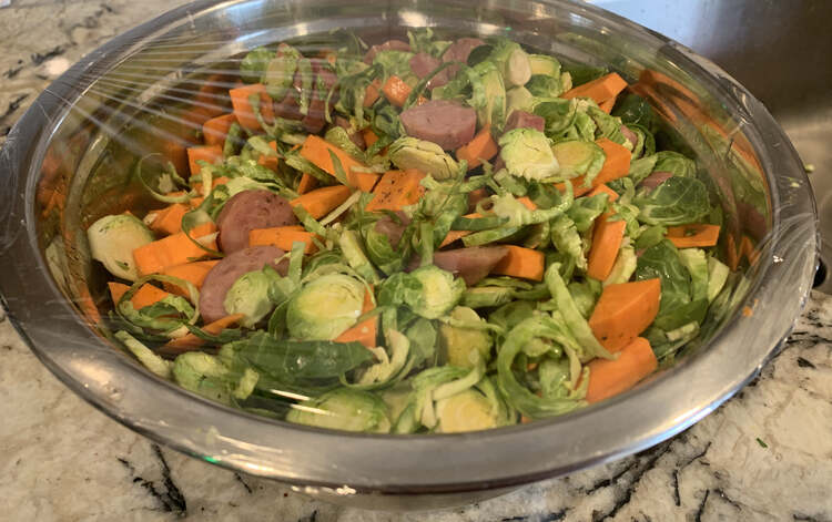Image shows a metal bowl filled with the evenly mixed Brussel sprouts, yams, sausages, salt, pepper, and avocado oil. Over the top a piece of plastic wrap is stretched across sealing it all in.