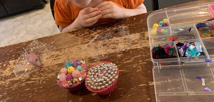Image shows two playdough filled cupcake liners decorated with beads. To the left sits an purple popsicle on plastic wrap. To the right sits the opened kit.
