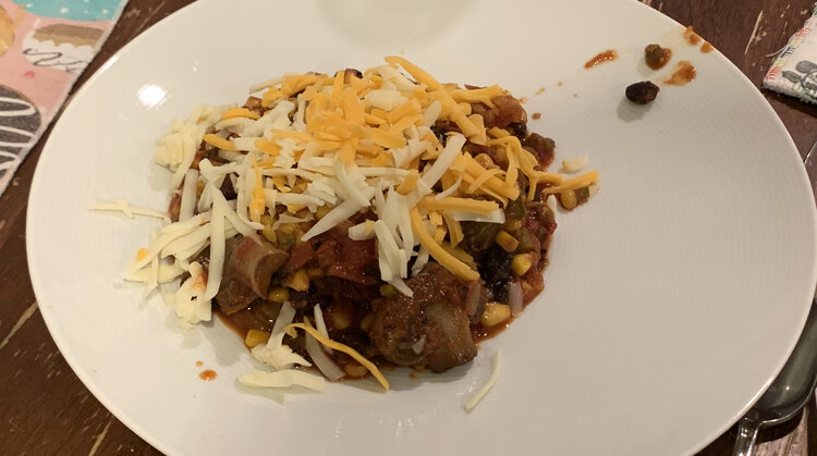 Image shows a plate with a mound of chili in the center covered in little pieces of orange and white cheese.