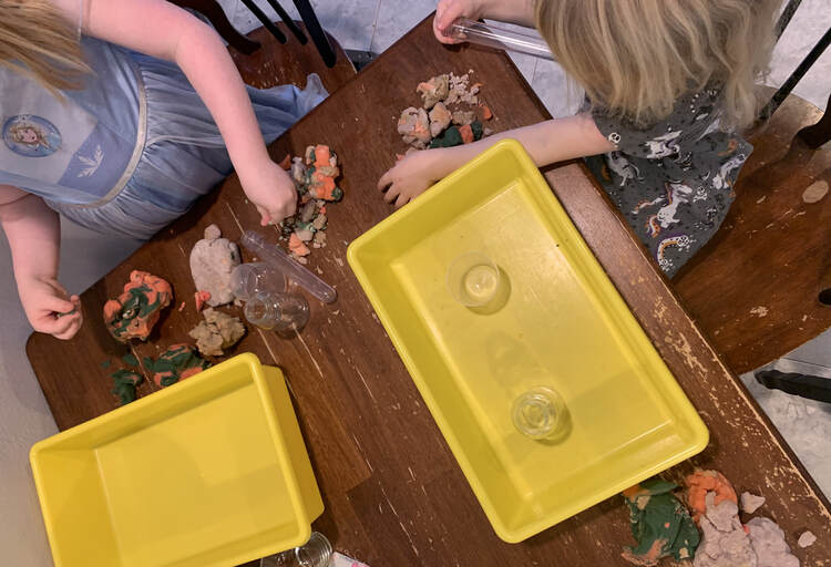 Image shows the kids set up at the end of the table. Both have a yellow bin in front of the and are planning their volcano.