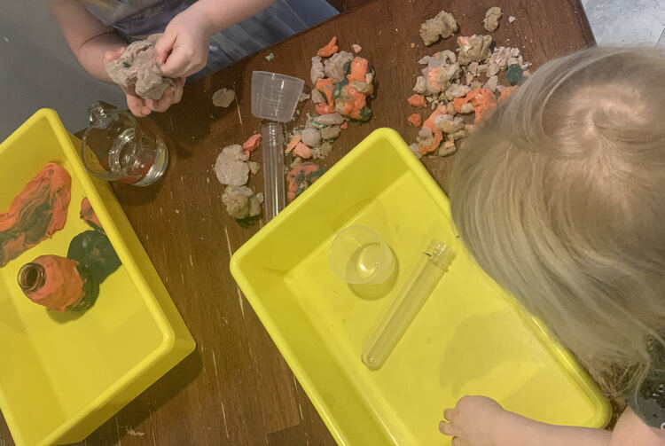 Image shows the girls. Zoey's yellow bin looks empty as her body blocks her glass jar. Ada has started out a playdough floor in the corner of her bin and started encircling her jar with black and pink playdough. She holds some dried grey-ish colored playdough.