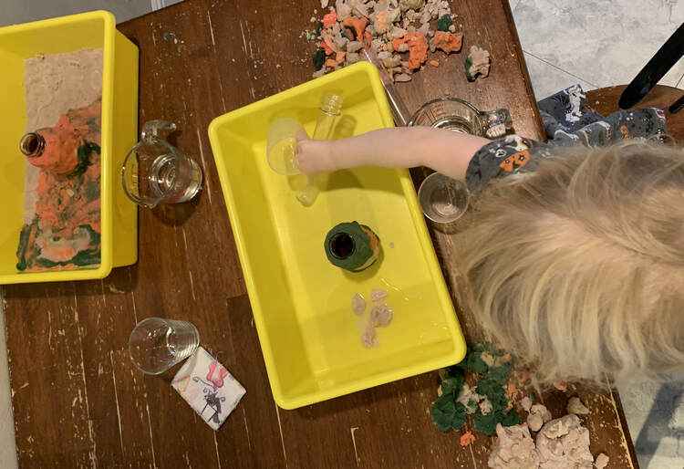 Image shows two yellow bins. The one to the left shows a grey, orange, and black playdough created floor with an orange volcano in the center. Zoey is leaning over the bin to the right moving the plastic containers as her playdough encased volcano sits in a pool of water.