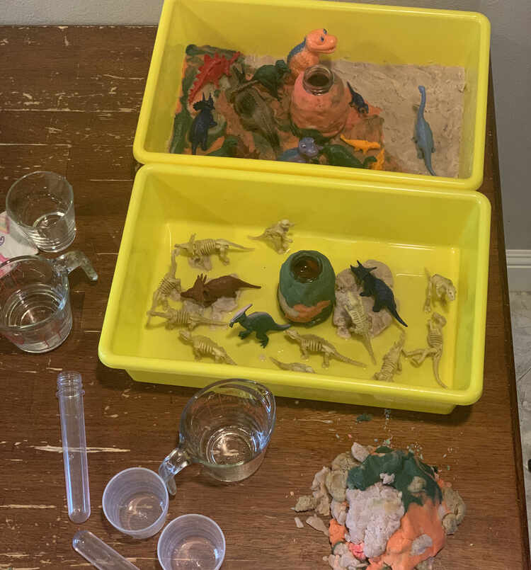 Image shows a view from above both plastic bins holding a dinosaur world. The top bin, further back, is Ada's filled with the playdough floor. There are colorful plastic dinosaurs in the land mostly on the black and orange section while a single Apatosaurus stands on the grey part. Zoey's looks mainly yellow as the only playdough in her bin is the volcano and several rocks. There are three solid colored dinosaurs and the rest are yellow skeletons. One dinosaur is on the pebbles, two on the rock, and the rest are in the water.