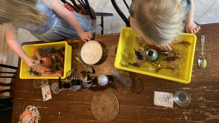 Image is taken from above at both girls' dinosaur worlds side by side. On the left Ada sprinkles a pinch of baking soda into her volcano while Zoey, on the right, plays with a dinosaur first.