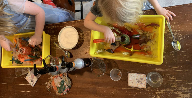 Image taken from above looking at the kids playing in their volcano sensory bin.