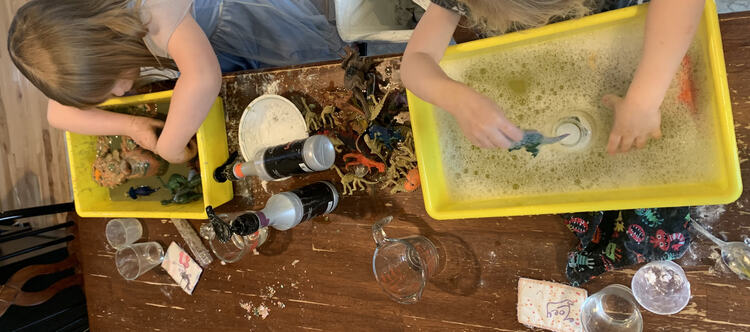 Image shows knocked over vinegar pump bottles, Ada playing in colored vinegar coated playdough dinosaur world, and Zoey with soapy water and cleaner dinosaurs.