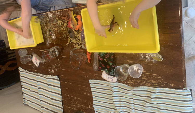 Image shows the entire table. Both girls have their hands in their bin with the dirty dinosaurs between them. The other side of the table has a clean tea towel laid out while between the two is their drinking glass (got dumped and a clean given), name tag, and extra tools.