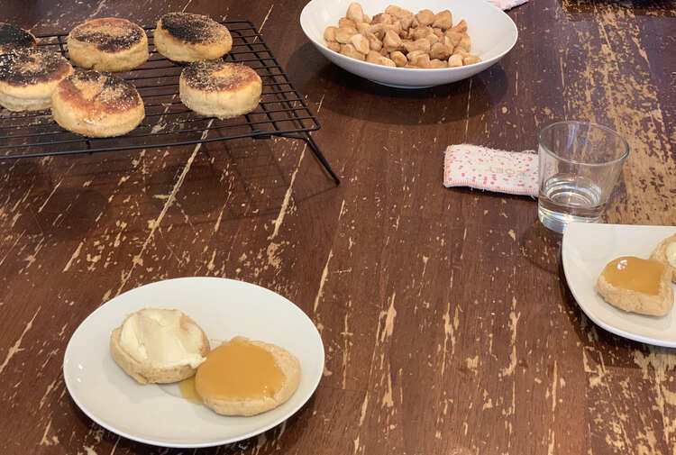 Image shows two saucers with a sliced open English muffin topped with cream cheese, on one, and lemon curd on the other half. In the background sits some burnt English muffins cooling on a wire rack and the bowl of baked scraps.