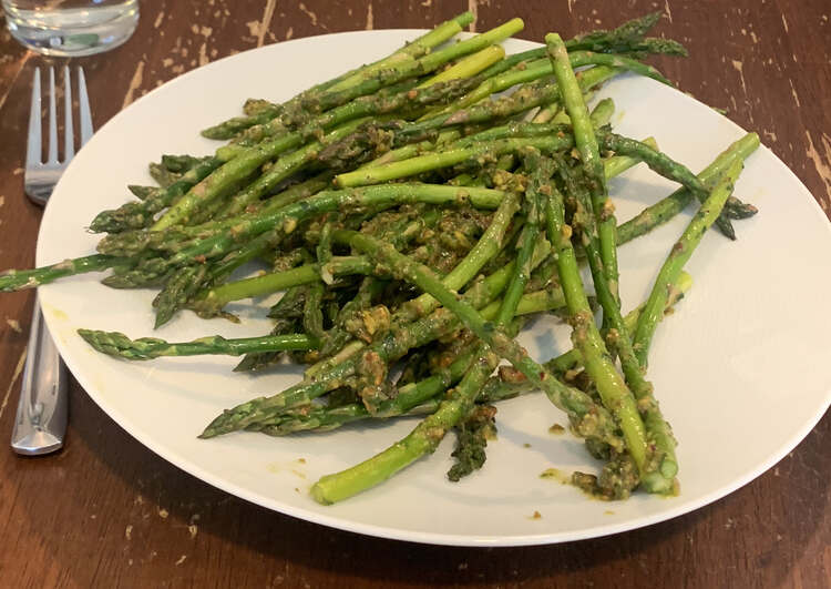 Image shows a white plate stacked with pistou coated asparagus. A fork is laid to the left.
