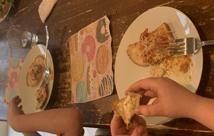 Image shows both of the kids' plates with two smaller slices of mix covered toast so they could try both flavors of bread. Ada has the toast up to her mouth while Zoey's reaching for her bread.