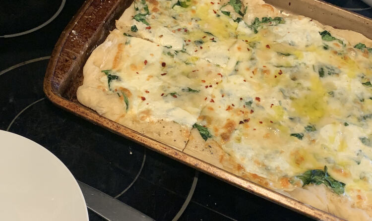 Image shows the final browned pizza sitting on a cookie sheet with the end cut into two pieces. A plate rests beside the cookie sheet.