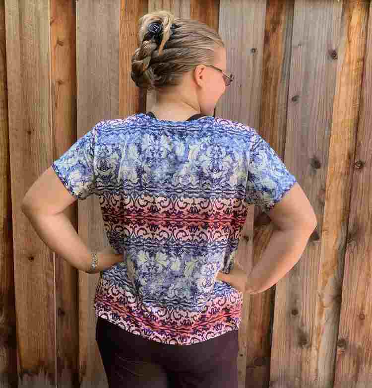 Me, a white woman, with my back to the camera as I face the wooden fence. My head is turned to the right and my hands are on my waist. The shirt is draping down from the shoulders and then bunched in at the waist under my hands.