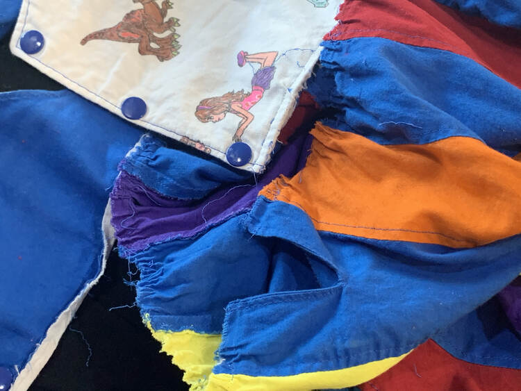 Image shows the back of a peppermint swirl dress with a white LEGO inspired and decorated bodice, blue snaps, and the orange, blue, red, yellow, and purple skirt separating from it.