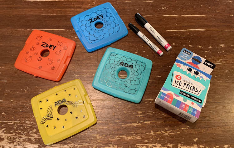 Image shows four decorated ice packs (orange, yellow, teal, and blue) alongside the empty packaging and two black oil-based sharpies.