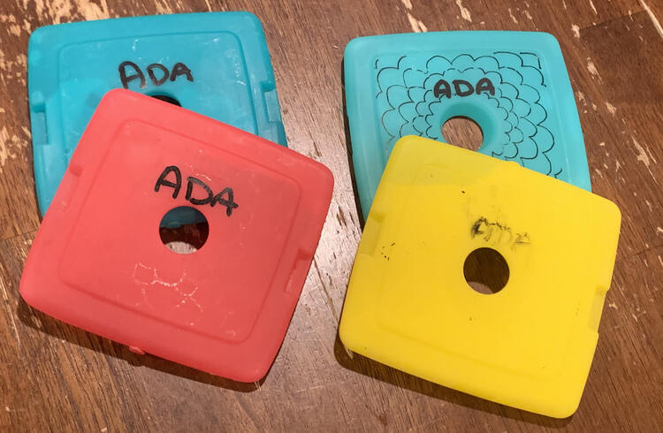 """Image shows four ice packs on the table. The two on the left show white remnants from where the original design was and are recently marked with """"Ada"""" in bold black paint. On the right is the newly flowered pack, behind, and a scrapped off yellow ice pack, in the front, with the word """"Ada"""" vaguely legible."""