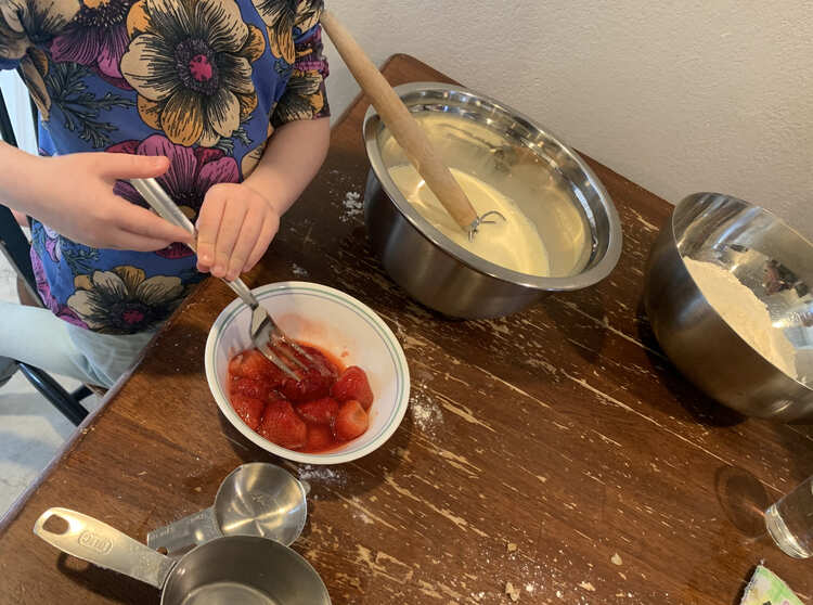 Zoey uses a fork to squish whole strawberries in a small bowl on the table. Behind it sits two large bowls one with wet ingredients and one with dry.