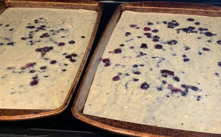 Image shows two cookie sheets side by side containing blue chunks and white batter with blue marbling.