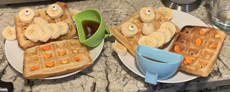 Image shows two saucers with two waffles each and a plastic dipper with syrup. One waffle on either plate holds pumpkin sprinkles while the other one looks like a person with banana ears, nose, mouth, and eyes.