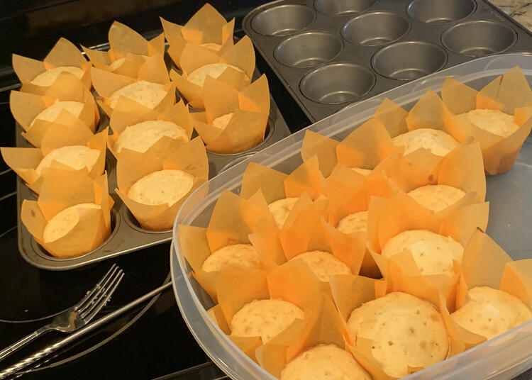 Image shows the baked cupcakes after they had cooled. There are two muffin tins in the background with one empty and the other mostly filled. In front sits a large plastic container half filled with the orange lined white cupcakes.
