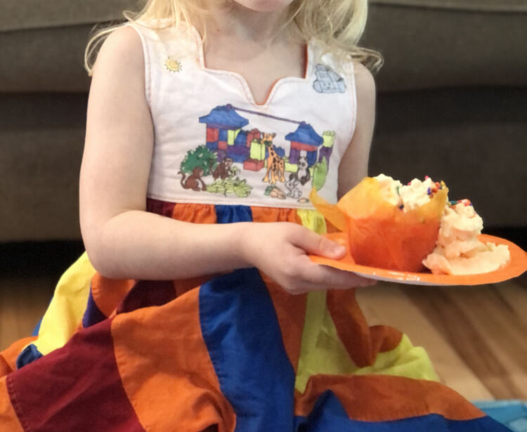 Image shows Zoey in a peppermint swirl dress holding an orange plate with a slightly blurred orange cupcake with orange whip cream and rainbow sprinkles on top.