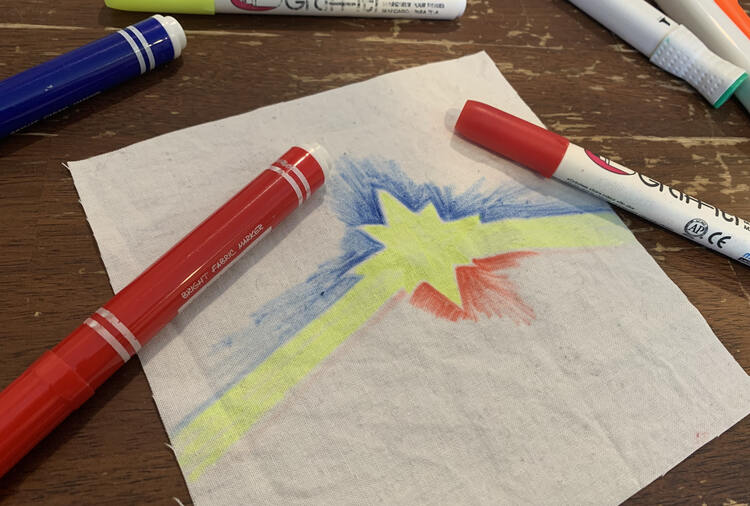 Image shows an upside down Captain Marvel logo on a square of white woven fabric. There are two red fabric markers laid over top.