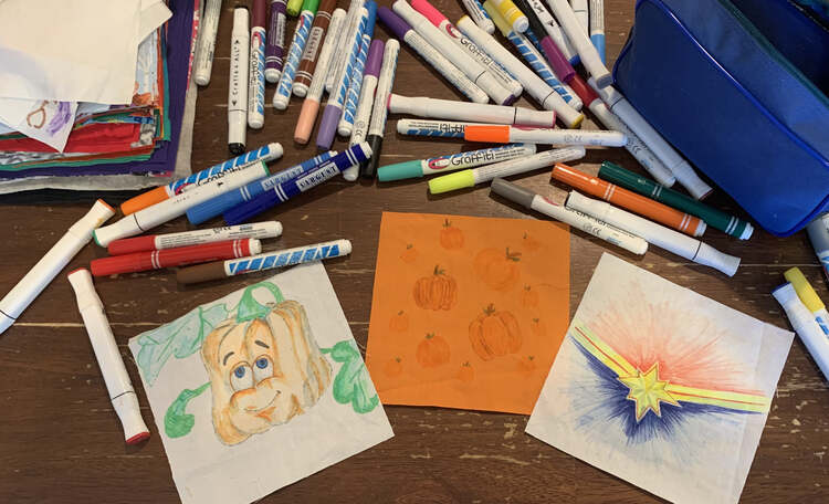Image shows the final three decorated squares of fabric that I drew on for the girls. In the center is an orange square with pumpkins while to the left there's a spookley on a white square and to the right a Captain Marvel logo. Above it lays an empty blue pencil pouch, a stack of the remaining masks, and lots of fabric markers.
