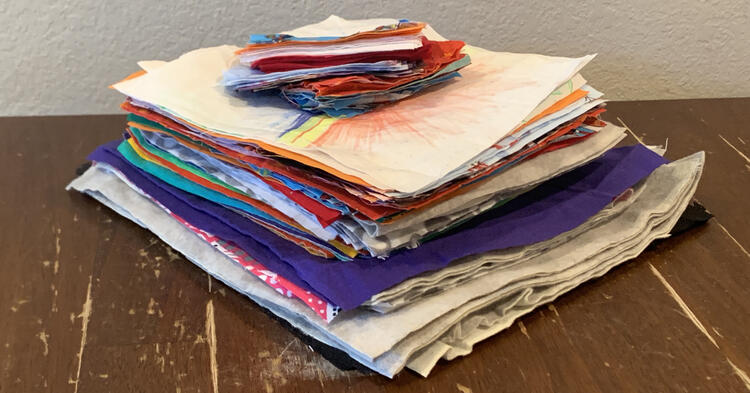 Image shows a stack of fabric squares with smaller rectangles on top. The larger ones squares are at the bottom with the small rectangles on top of the smaller squares of fabric.