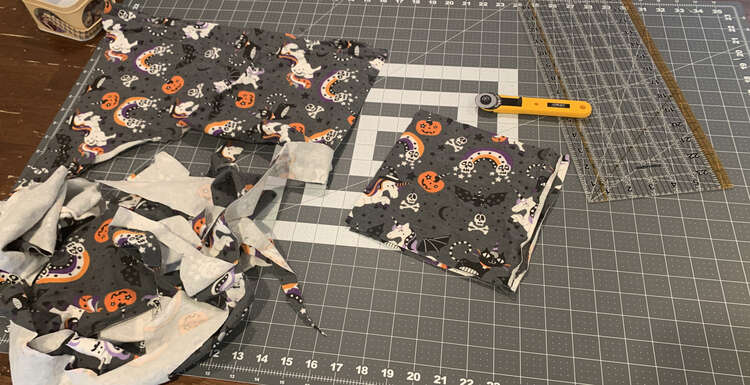 Image shows a large scrap of fabric with Halloween unicorns and unicorn kitties, and unicorn pumpkins along with bats, skulls, and rainbows.