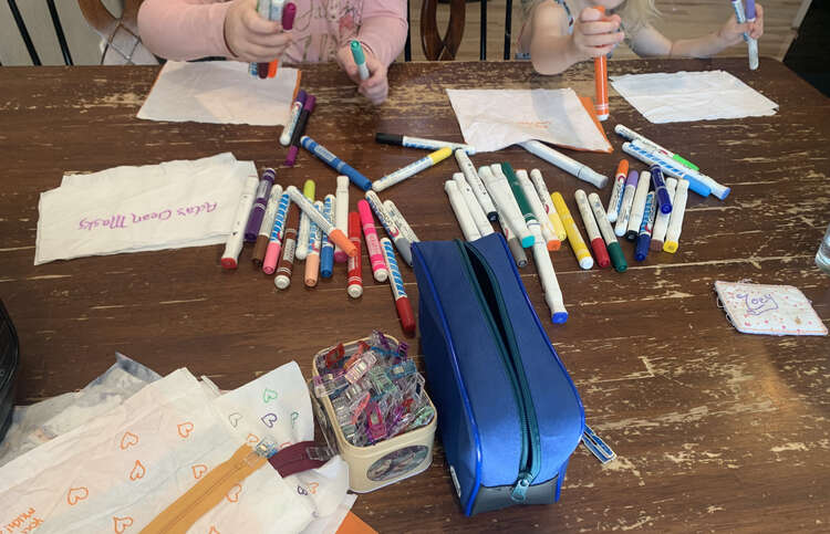 Image shows the kids grabbing fabric markers from a pile in the center while white rectangles of fabric sit in front of them. Closer to the bottom sits a pile of clips, and empty pouch, and a stack of fabric and zippers.