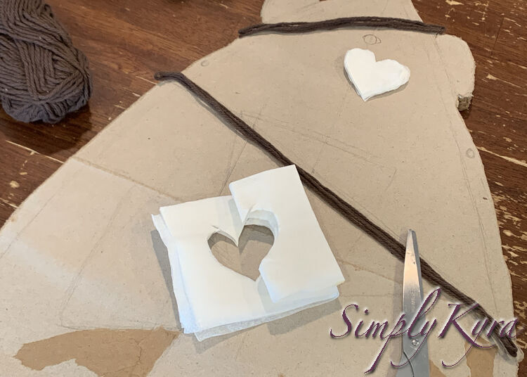 Image shows the skateboard with a small stack of heart shaped napkin layers placed next to the ink-marked circle. Near the bottom of the photo you can see the scissors and the rest of the napkin with the heart cut from the center.