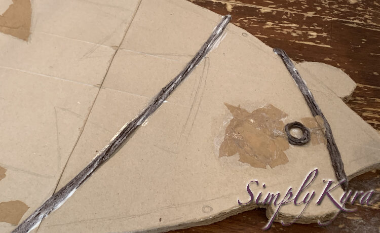 Image shows the white napkin and top connection covered in light brown paper. The yarn necklace and circle is still uncovered and visible.