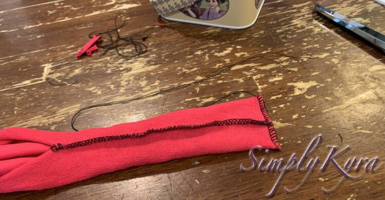 Image is similar to the previous one but now the end is serged with black threads rather than clipped closed. The bottom side already had the serger tail tied and trimmed while the top one sports unraveled threads.