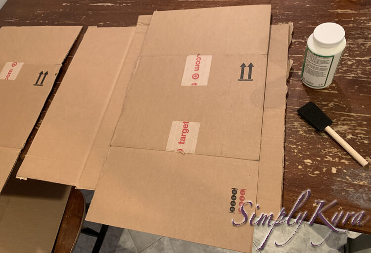 Image shows one larger square of cardboard underneath with a smaller rectangular Target box covering the right side. The other piece is to the left while a bottle of Mod Podge and a foam brush lay to the right.