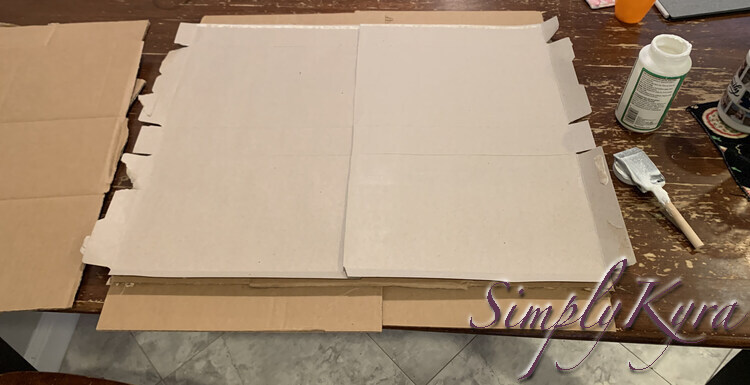 Image shows the lightened cardboard square with the two cereal boxes glued down side by side and slightly overlapping.