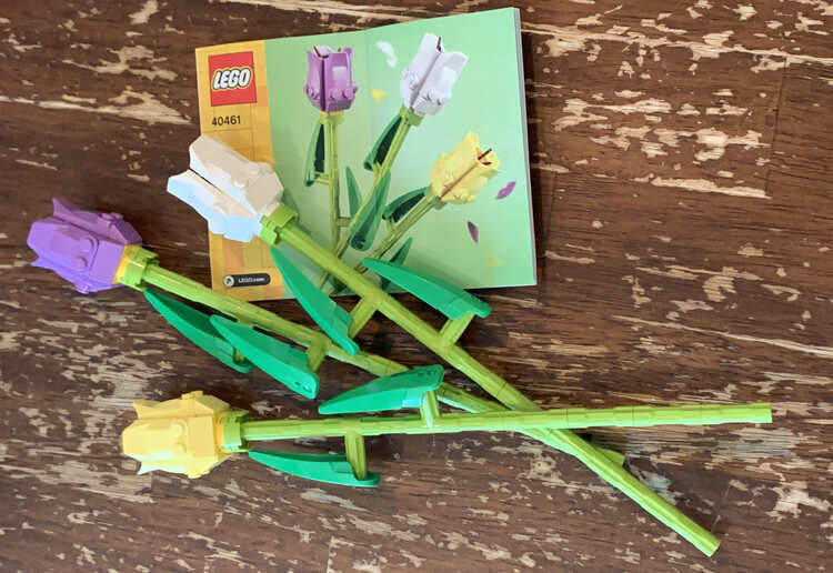 Image shows the three final tulips laid out on the table and tilted so the stems overlap under the leaves. The instruction book is below the white tulip with the lavender and then yellow tulip below.
