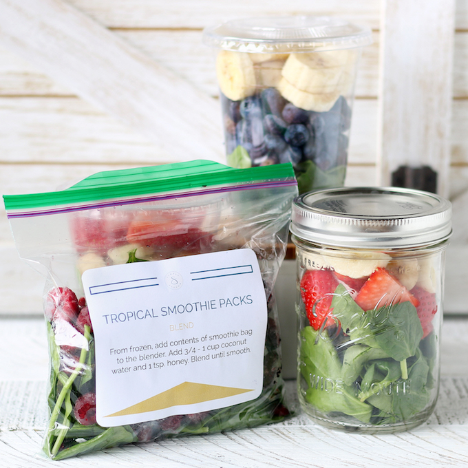 Meal Prep Freezer Smoothie Packs packaged in an assortment of containers. Mason jar, plastic bag and plastic cup.
