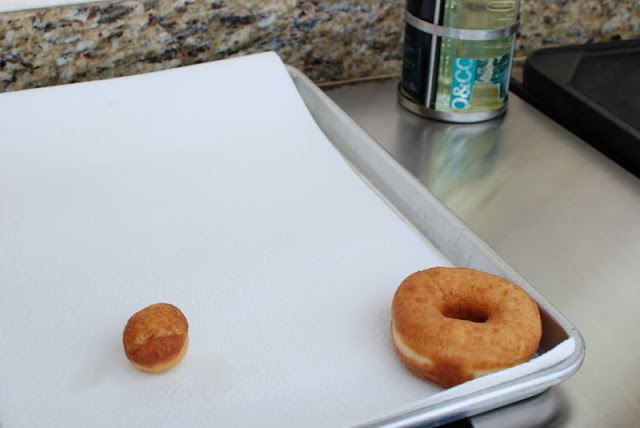 Baking sheet lined with a paper towel with a spudnut and donut hole draining