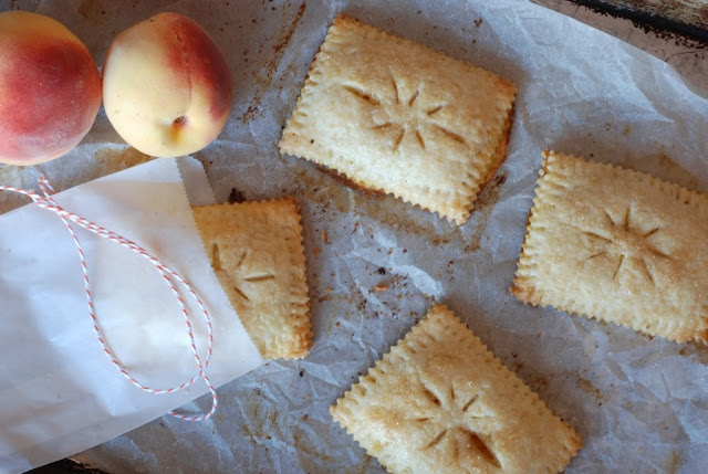 four hand peach pies on baking sheet with a peach and red and white twine