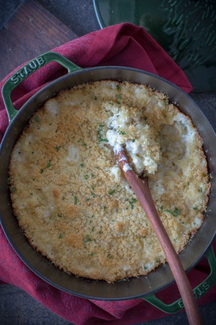 Baked macaroni and cheese with a wooden spoon