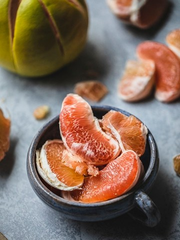 Pomelo is a tropical fruit from the citrus fruit family. A pomelo looks very similar to grapefruit but slightly larger in size. Their outer shell is usually light green and has a very thick fibrous peel, native to South and Southeast Asia. #pomelo #citrusfruit #healthyfruit #pomelosalad