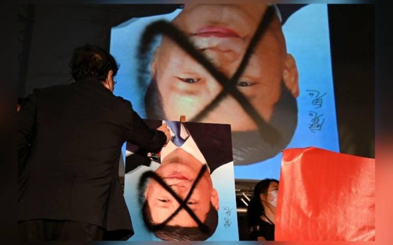 Seorang penunjuk perasaan menyembur poster Presiden China, Xi Jinping di luar Parlimen di Taipei. - AFP