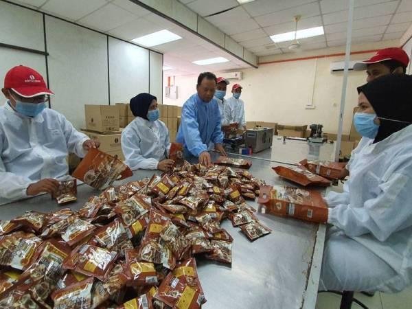 Mohd Zaki (tiga dari kiri) meninjau pekerja yang sedang melakukan proses pembungkusan kopi.