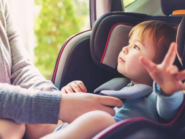 60979523 – toddler girl buckled into her car seat